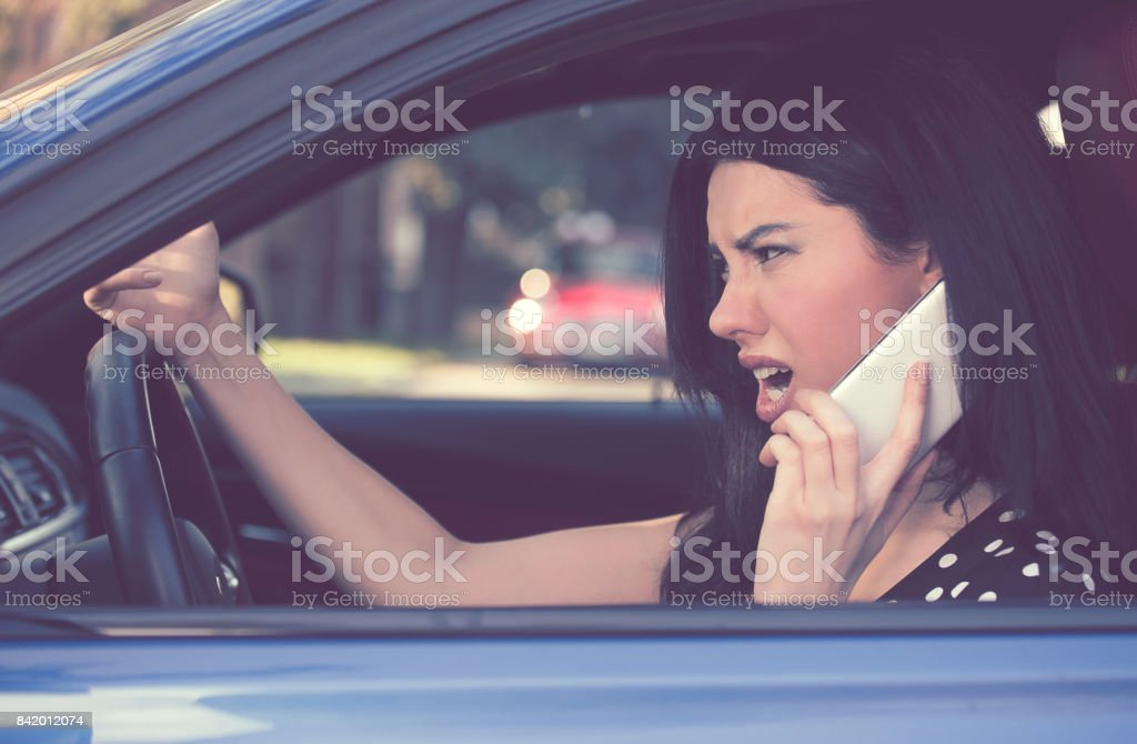 Side profile angry driver woman talking on mobile phone. Negative human emotions face expression stock photo
