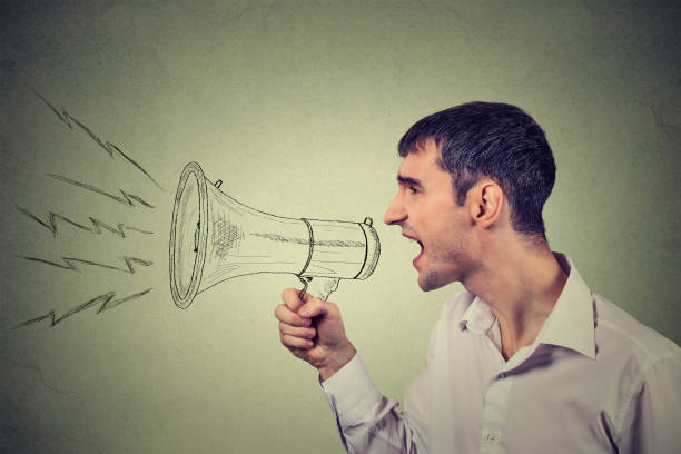 Side profile business man shouting into a megaphone stock photo