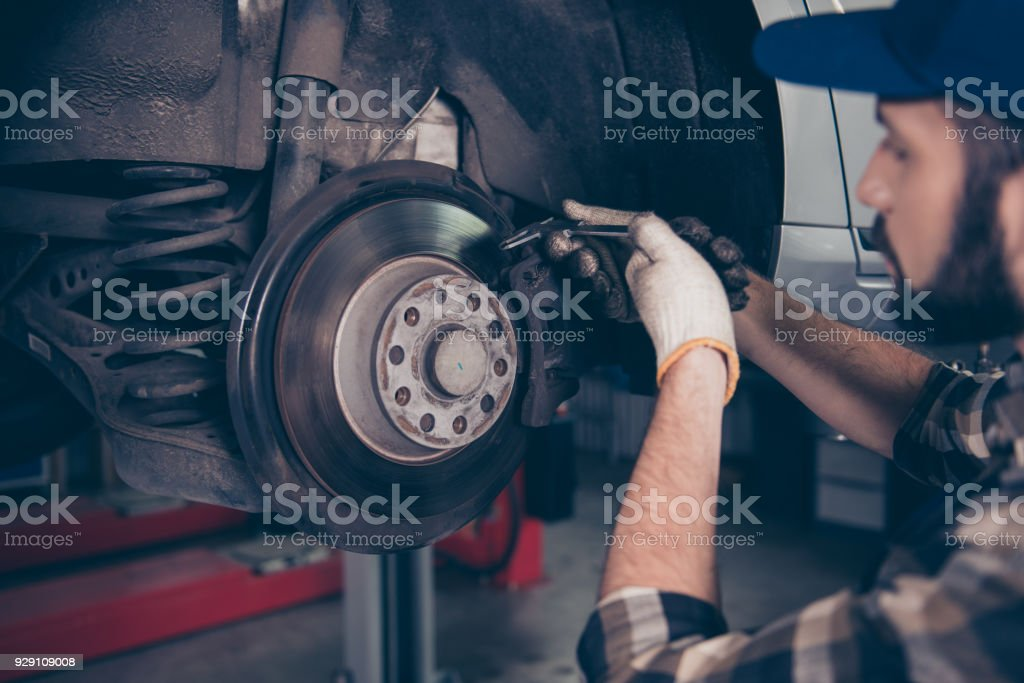 Side profile close up shot of expert specialist technician changes tires, tyres or brake pads of lifted up car, at auto workshop, wears checkered shirt, uniform costume, hat headwear stock photo