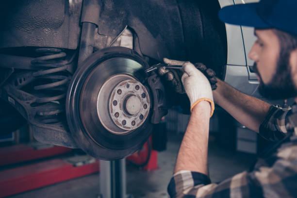 側面輪廓特寫鏡頭專家專家技術員改變輪胎, 輪胎或刹車墊的舉起汽車, 在汽車車間, 穿著格子襯衫, 制服服裝, 帽子帽 - 剎車制 個照片及圖片檔