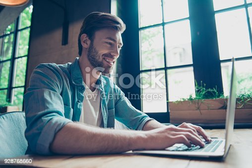 istock Side profile low angle shot of cheerful man smiling, searching information on his device in nice modern work station, in casual smart wear, grin, big windows with green nature view 928768660