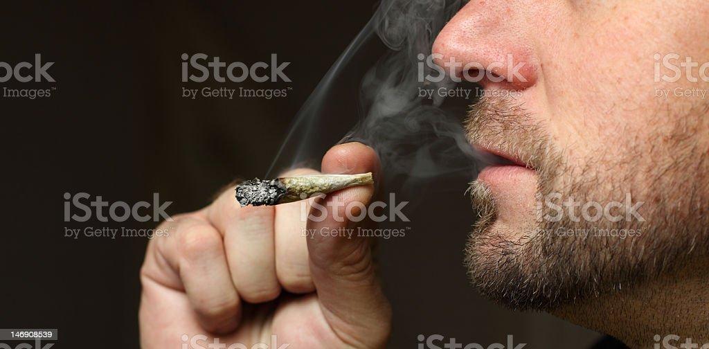 Side profile of a bearded man smoking a marijuana joint royalty-free stock photo