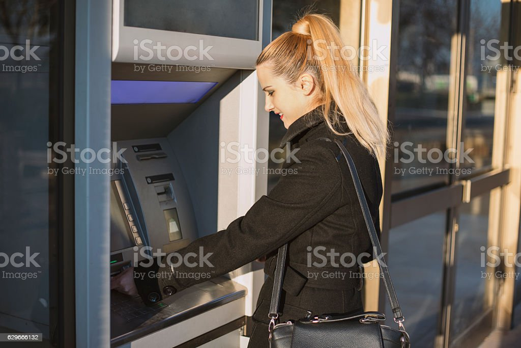Side profile of a businesswoman using an ATM stock photo