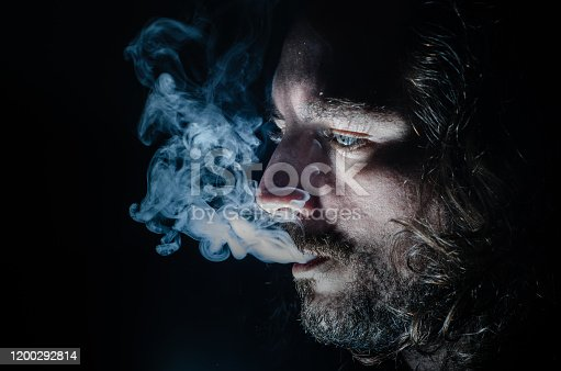 689660424 istock photo Side profile of a smoking man in low key exhaling, islolated, with copy space. 1200292814