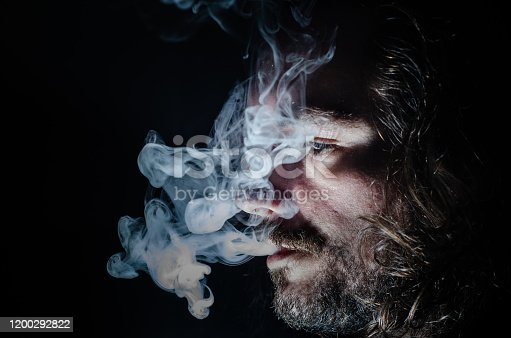 689660424 istock photo Side profile of a smoking man in low key exhaling, islolated, with copy space. 1200292822