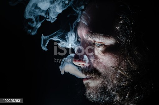 689660424 istock photo Side profile of a smoking man in low key exhaling, islolated, with copy space. 1200292831
