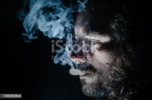 689660424 istock photo Side profile of a smoking man in low key exhaling, islolated, with copy space. 1200292844