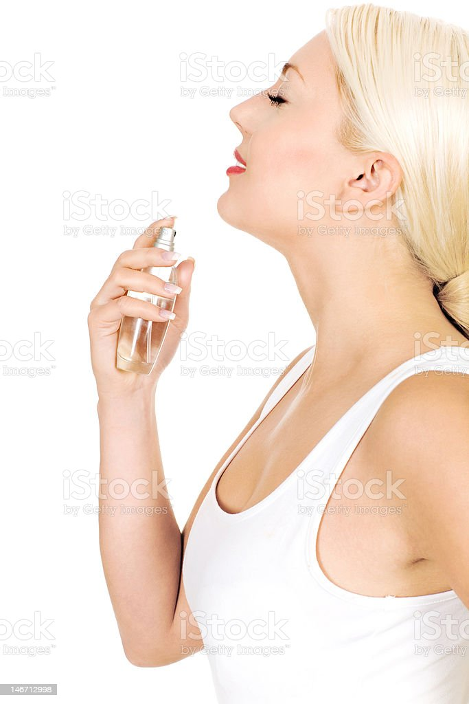 Side profile of a woman spraying perfume on her neck royalty-free stock photo