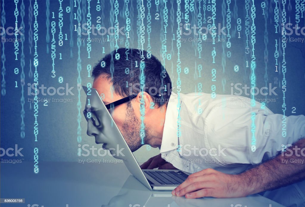 Side profile of a young business man with his face passing through the screen of a laptop on binary code background stock photo