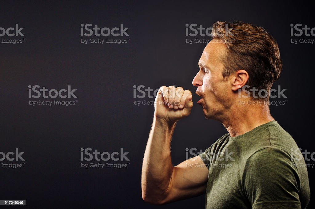 Side profile of man as he is coughing stock photo