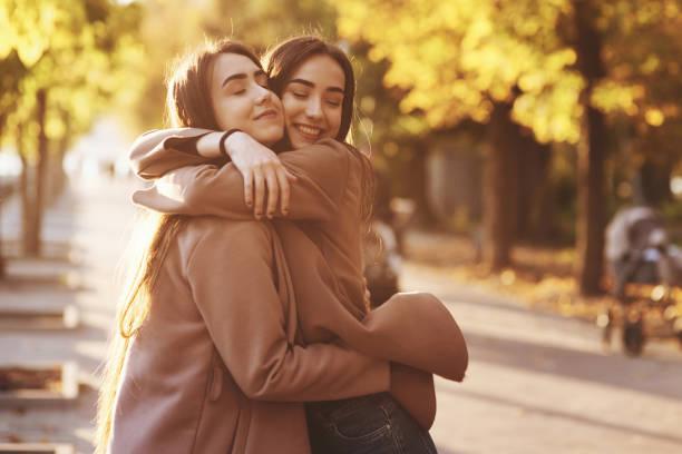 Seitenprofil von jungen, hübsch lächelnden Brünette-Zwillingsmädchen, die sich umarmen und sich in lässigem Mantel, der in der sonnige Parkanlage im Herbst beieinander steht, vergnügen. – Foto