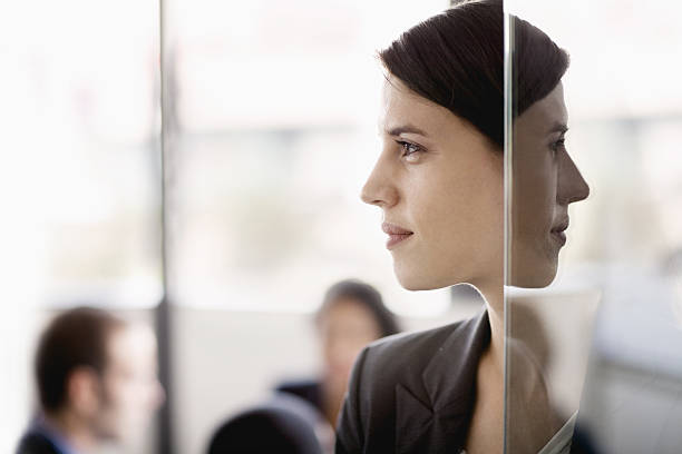 side profile on a businesswoman with coworkers in the background - symmetry stock photos and pictures