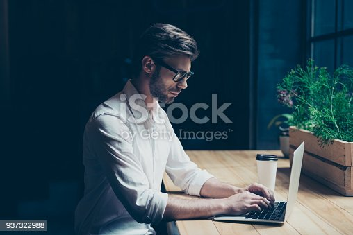 937328186 istock photo Side profile photo of a ponder young man in formal wear, sitting at his work place in a loft styled modern coworking and looking at the computer, typing 937322988