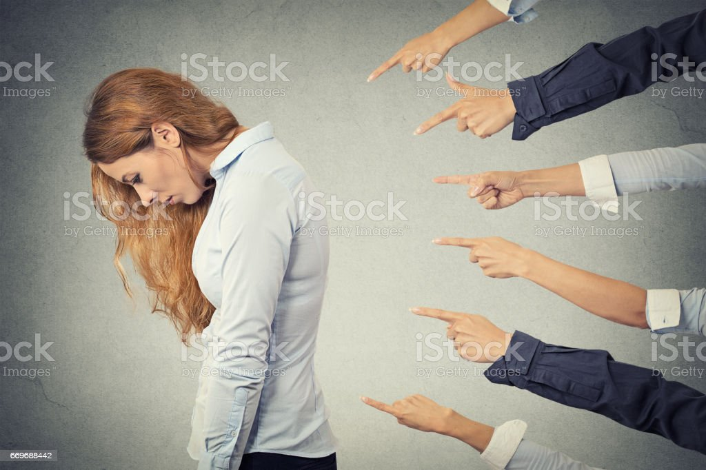 Side profile sad upset woman looking down many fingers pointing at her stock photo