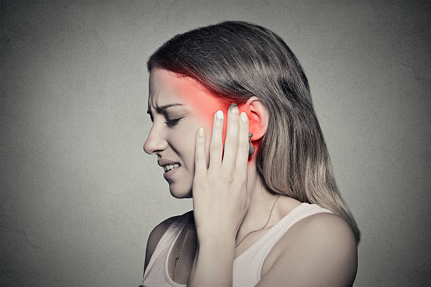 side profile sick female having ear pain touching head Tinnitus. Closeup up side profile sick female having ear pain touching her painful head temple isolated on gray wall background human ear stock pictures, royalty-free photos & images