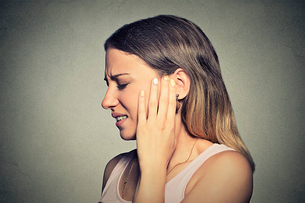 side profile sick young woman having ear pain - ear stock photos and pictures