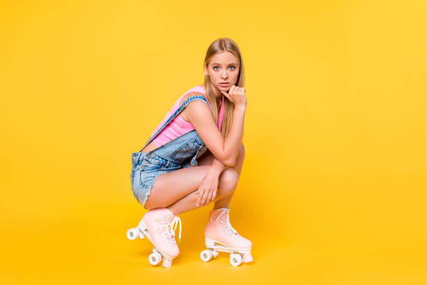Side profile turned hajf view portrait photo of charming pretty beautiful attractive cute lovely confident roller skater wearing pink shoes isolated on yellow background copy space stock photo