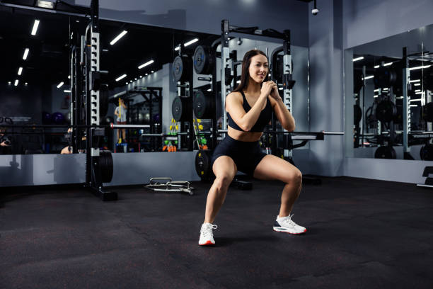 A side profile view of a smiling girl in a sports bra and shorts does deep situps with her arms crossed in a darkened indoor gym. Love sport, challenge stock photo