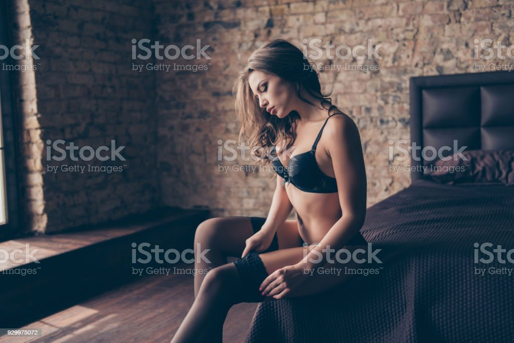 Side profile view of attractive stylish brunette prostitute in black silk bra, panties, tights, waiting for lover in loft room, brick walls, so fit, muscular, adorable, preparing hor sex, brown bed stock photo
