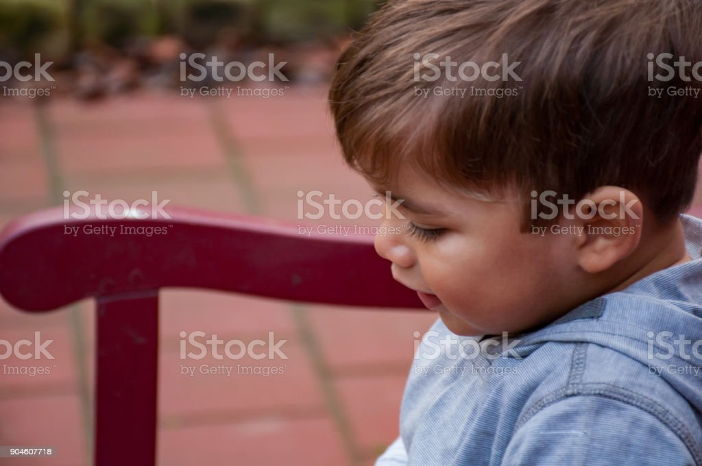 Side profile view of one-year-old boy sitting on bench stock photo