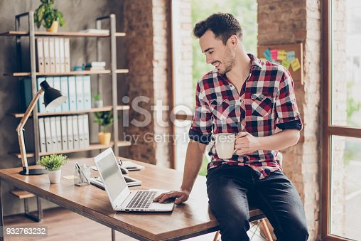 932763106 istock photo Side profile view of successful happy brunet student, sitting on top of his desk, smiling, having hot tea, typing on computer, in casual wear, at his work station 932763232