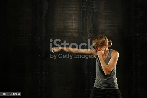 497607484 istock photo Side profile view of young athletic women boxing 1011266834