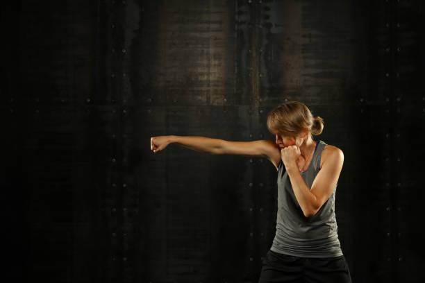 profiel-zijaanzicht van jonge sportieve vrouwen boksen - menselijke arm stockfoto's en -beelden