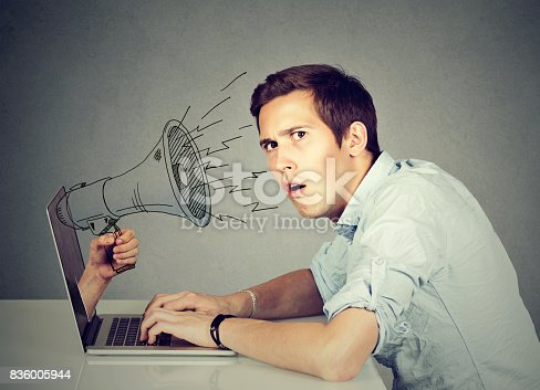 istock Side profile young anxious man sitting at table using working on a computer with megaphone poking out from a laptop screen 836005944