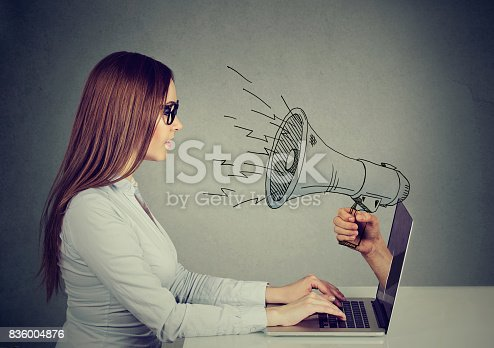 istock Side profile young woman in glasses sitting at table using working on a computer with megaphone poking out from a laptop screen 836004876