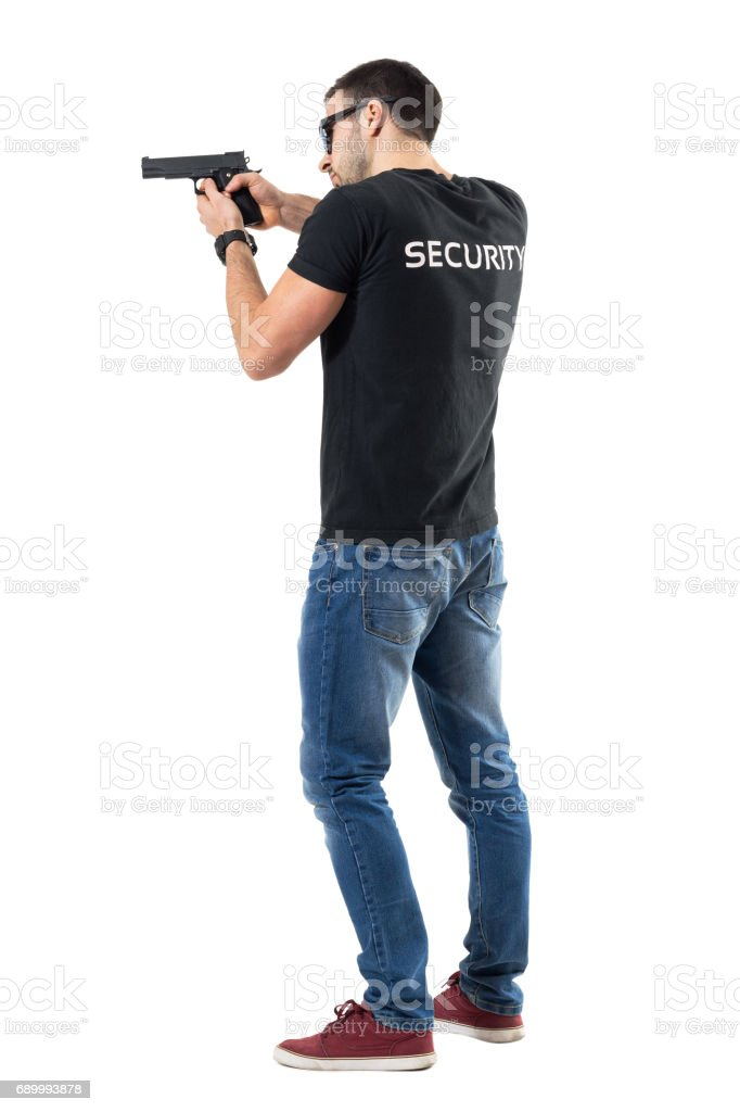 Side rear view of security guard pointing and aiming gun away stock photo