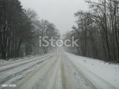 657042754 istock photo Side road in the forest in winter 669118430
