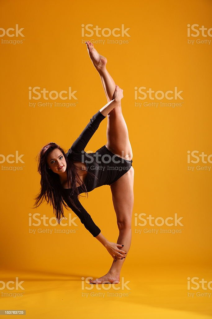 Side splits dance pose by beautiful woman against yellow background royalty-free stock photo