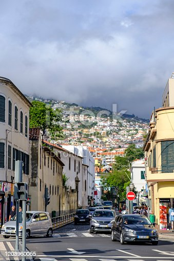 Side street of the Rua de Janeiro next to the Ribeira de Santa Luzia in Funchal on Madeira island during summer day. Rua 31 de Janeiro is one of the leading and most extensive streets of Funchal. People are walking on the sidewalk.