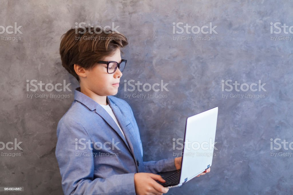 側面視圖在可愛的青少年男孩與筆記本電腦對牆 - 免版稅互聯網圖庫照片