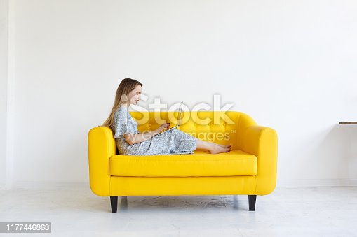 Side view. Beautifull charming girl checks email online, uses modern laptop computer, works remotely, uses wifi. Nice-looking woman smiling sits on yellow sofa at home over white background. Copyspace