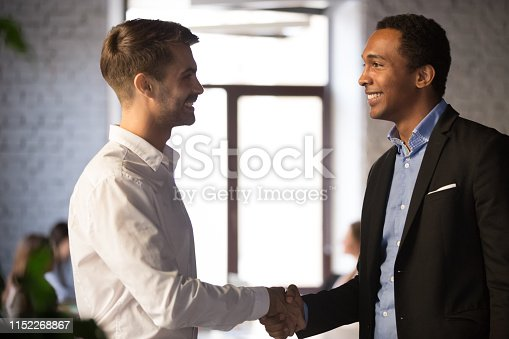 924520144 istock photo Side view black and caucasian businessmen shaking hands 1152268867