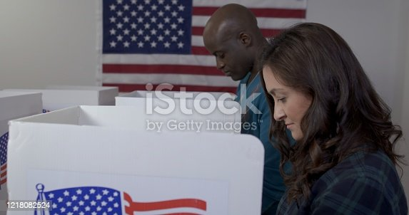 MS side angle view Caucasian woman and African American man casting votes in booths at polling station.