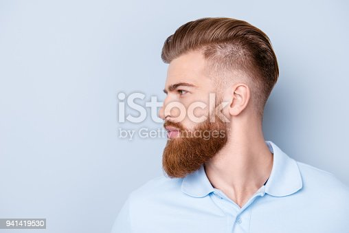 istock Side view close up portrait of handsome bearded young serious man in polo isolated on copyspace 941419530