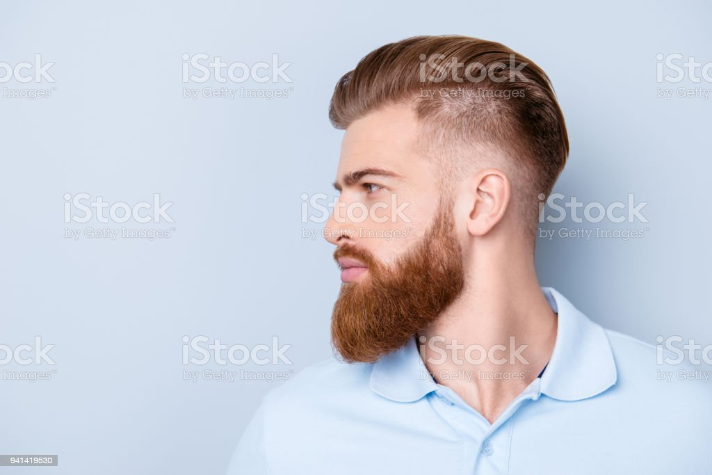 Side view close up portrait of handsome bearded young serious man in polo isolated on copyspace stock photo