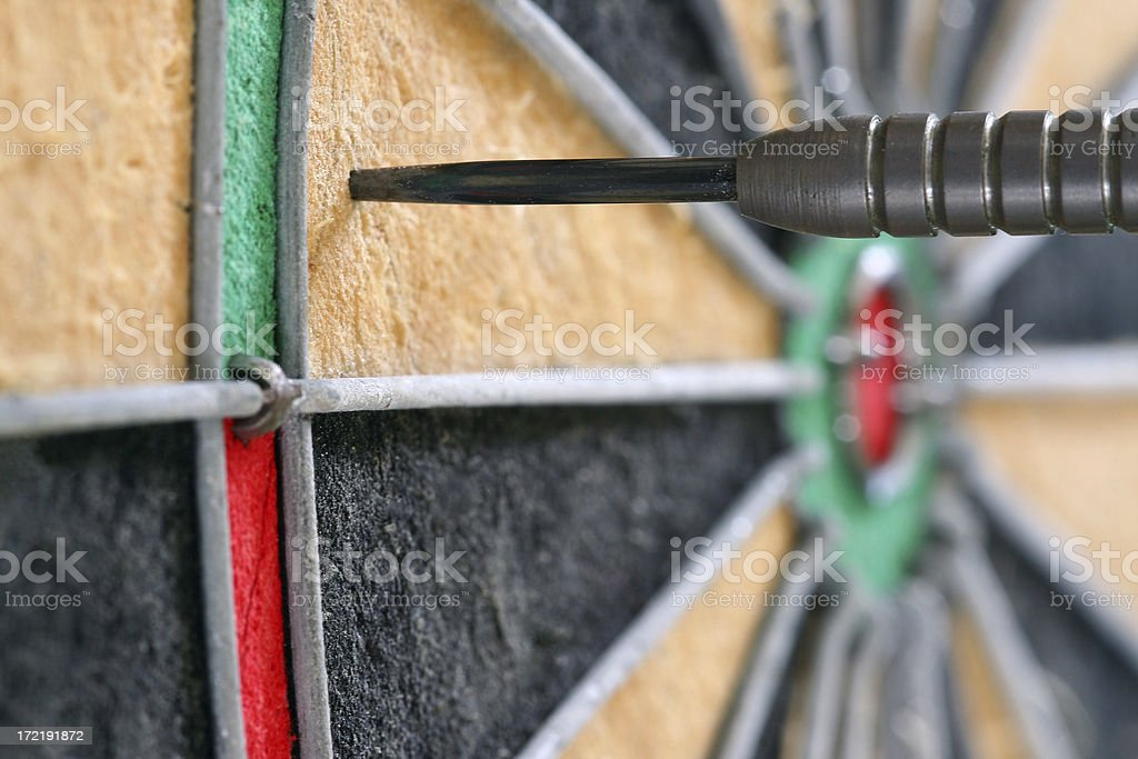 Side view close-up of single dart in a dartboard royalty-free stock photo