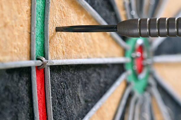 seitenansicht nahaufnahme von einem dart auf die dartscheibe - eisenmangel was tun stock-fotos und bilder