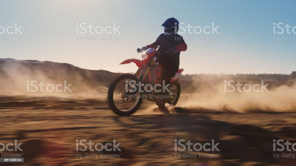 Side View Footage of the Professional Motocross Motorcycle Rider Driving on the Dune. It's Sunset and Track is Covered with Smoke/ Dust/ Dirt. Blur motion. stock photo