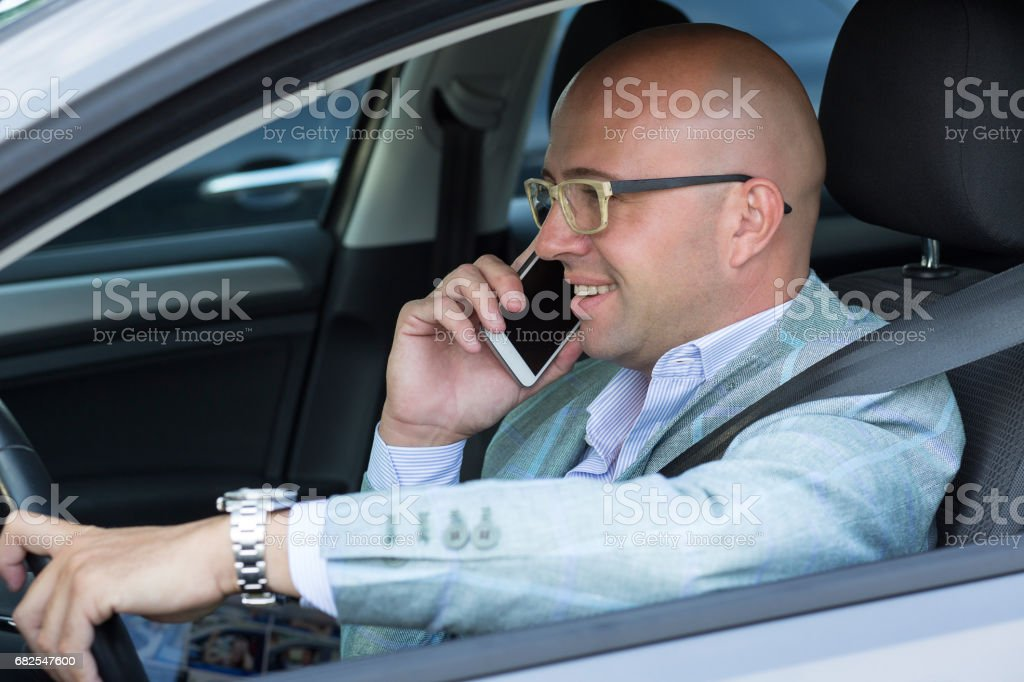 side view handsome successful young man smiling talking on mobile phone while driving his car . Risky, reckless driver bad habits. Traffic safety rule violation lack of attention concept stock photo