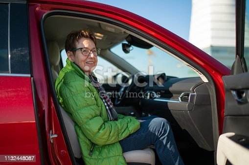happy smiling senior woman 70 years old sitting at passenger side car door open on sunny winter day on parking space, shallow focus