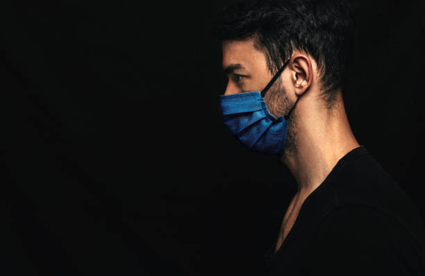 Side view image of Caucasianman wearing medical blue mask on the face during virus pandemic lockdown posing on the black wall with copy space. Male with disposable face mask to prevent the coronavirus stock photo