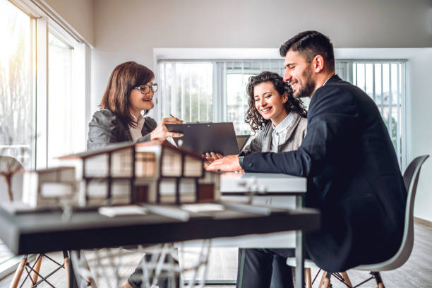 Side view image of young happy family sitting in consulting office, making property purchase. Mature female realtor helping business couple do financial investment. Installment payment, mortgage, loan for estate concept stock photo