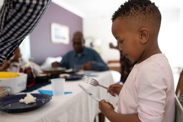 side view liten flicka överväger kniv och gaffel vid matbordet - bordsskick bildbanksfoton och bilder