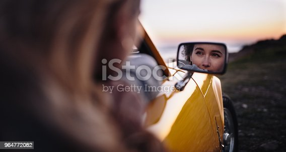 147878016 istock photo Side view mirror reflection of woman sitting in vintage car 964772082
