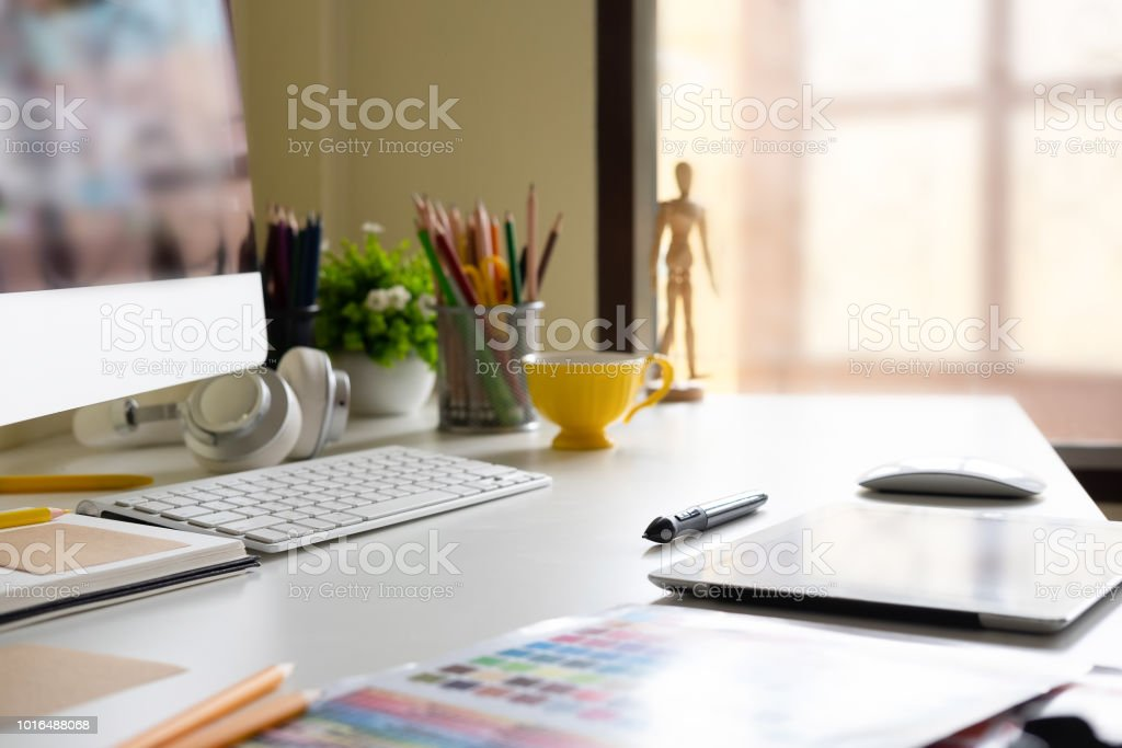 Side view Modern office workplace with digital tablet, notepad, colorful pencils, computer in morning. royalty-free stock photo