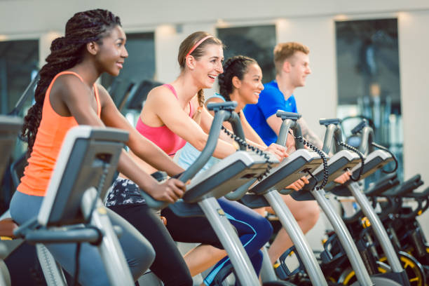 Side view of a beautiful woman smiling while cycling during exercising class at the gym stock photo